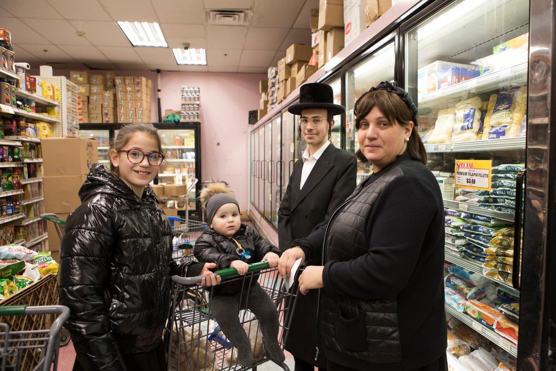 Toby, Shlomo, Dov en Rifka (van links naar rechts) doen boodschappen in de 'All Fresh Supermarket' in Monsey, Rockland County, een supermarkt die onlangs is blootgesteld aan de mazelen. De kinderen zijn ingeënt tegen de mazelen.  Beeld Chantal Heijnen