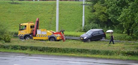 Auto glijdt van de weg en blijft hangen op de vangrail