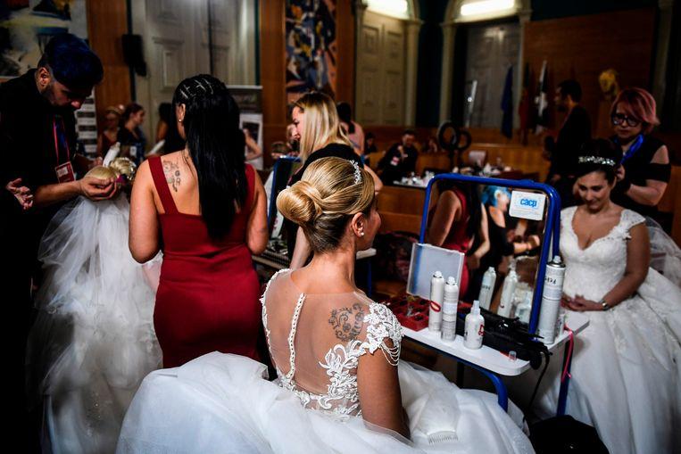 Portugese bruiden maken zich klaar voor hun huwelijk op een ceremonie waarbij elf paren tegelijk in het huwelijk treden. Zij doen dat op de dag van Sint Antonius, beschermheilige van de hoofdstad Lissabon. Het is al jarenlang traditie dat een huwelijk op deze dag gratis is.  Beeld AFP