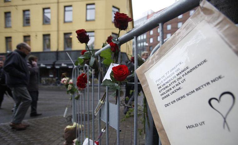 Mensen bevstigen rozen aan de dranghekken voor de rechtbank van Oslo. Beeld reuters