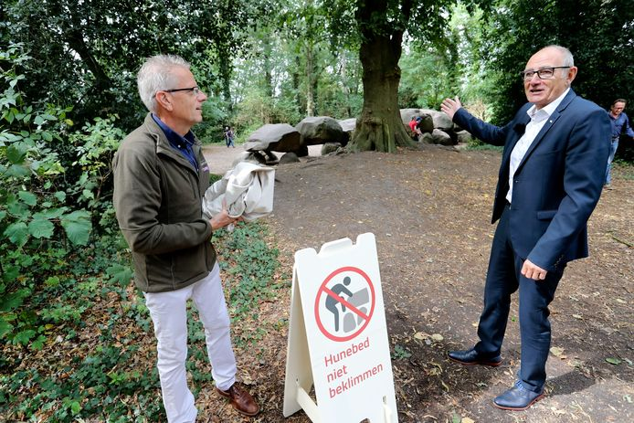Teddy Bezuijen van het Drents Landschap en zanger Egbert Meyers  onthullen in Borger een waarschuwingsbord tegen het beklimmen van hunebedden.
