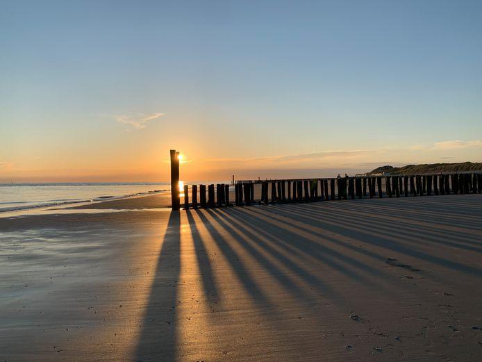 LANGE SCHADUWEN De paalhoofden op het strand van Vlissingen trekken lange schaduwen in de ondergaande zon.