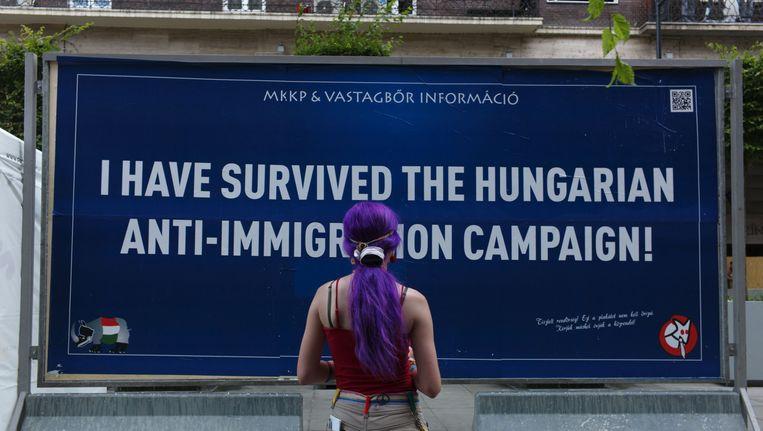 Een vrouw kijkt naar de pro-immigratieposter in Budapest. Beeld ap