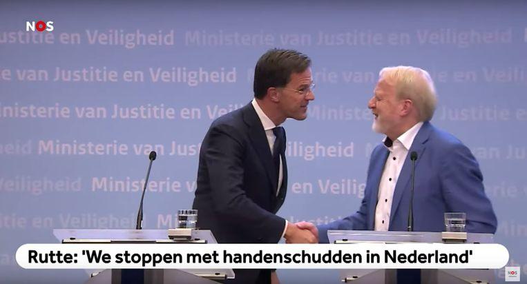 Premier Rutte schudt per ongeluk toch de hand van Jaap van Dissel (RIVM). Beeld NOS