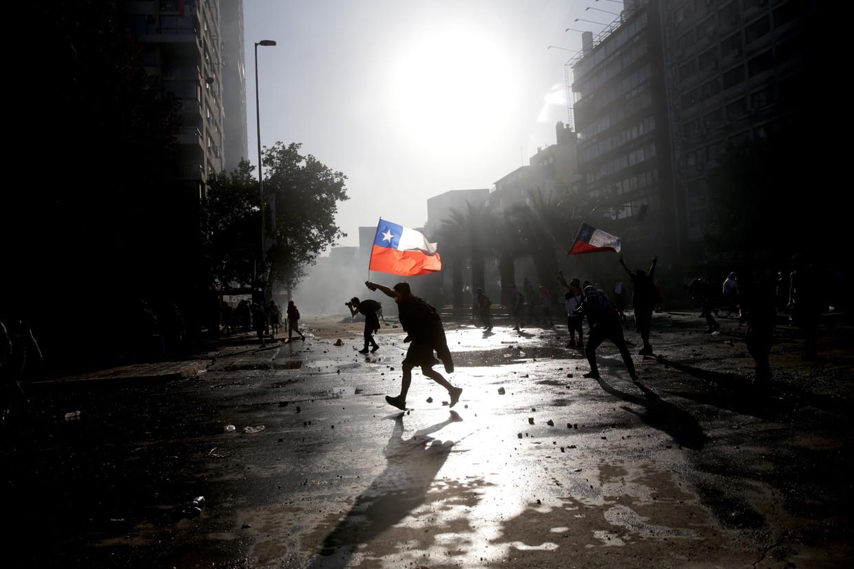 Protestanten in de straten van Chili. Met tienduizenden gaan de Chilenen dagelijks de straat op om een beter leven te eisen: hogere pensioenen en minimumlonen, goedkoper onderwijs en een betaalbare gezondheidszorg. Beeld null