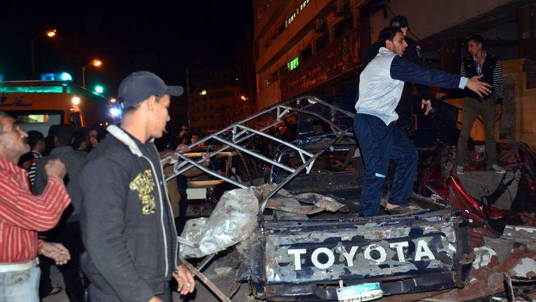 Mensen bekijken het resultaat van een bomaanslag in Mansoura, Egypte eind vorig jaar, mogelijk uitgevoerd door Ansar Beit al-Maqdis. Beeld EPA