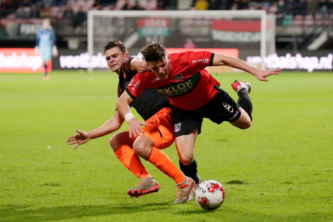 Ole Romeny van NEC wordt van de bal gezet door Rico Zeegers van Jong PSV.