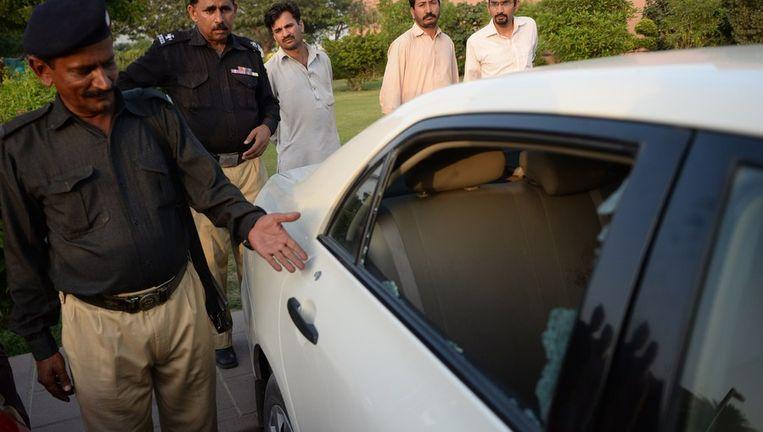 Een Pakistaanse politieman wijst op een kogelgat in het portier van de auto waarin Hamid Mir zat toen hij werd beschoten. Beeld afp