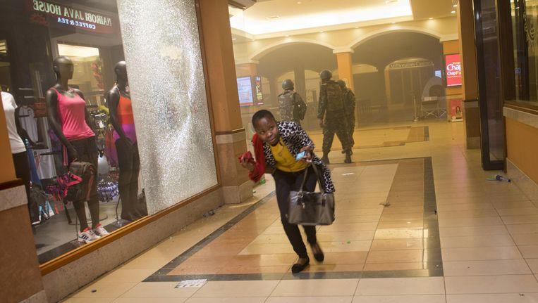 Een vrouw zoekt een veilig heenkomen terwijl de aanval in winkelcentrum Westgate in Nairobi in volle gang is. Beeld ap
