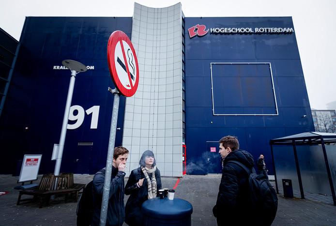 Leerlingen van de Hogeschool Rotterdam roken buiten een sigaret. Na de zomervakantie moet het terrein van de Hogeschool volledig rookvrij worden gemaakt.