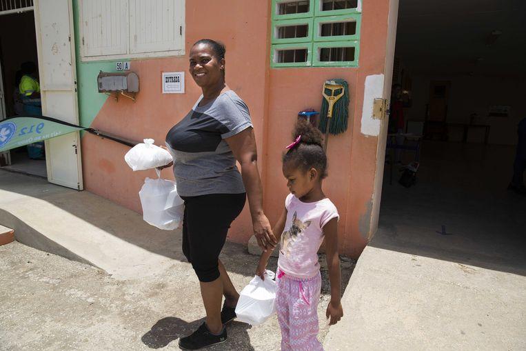 Bewoners van Willemstad krijgen voedselpakketten bij het wijkcentrum.  Beeld ANP