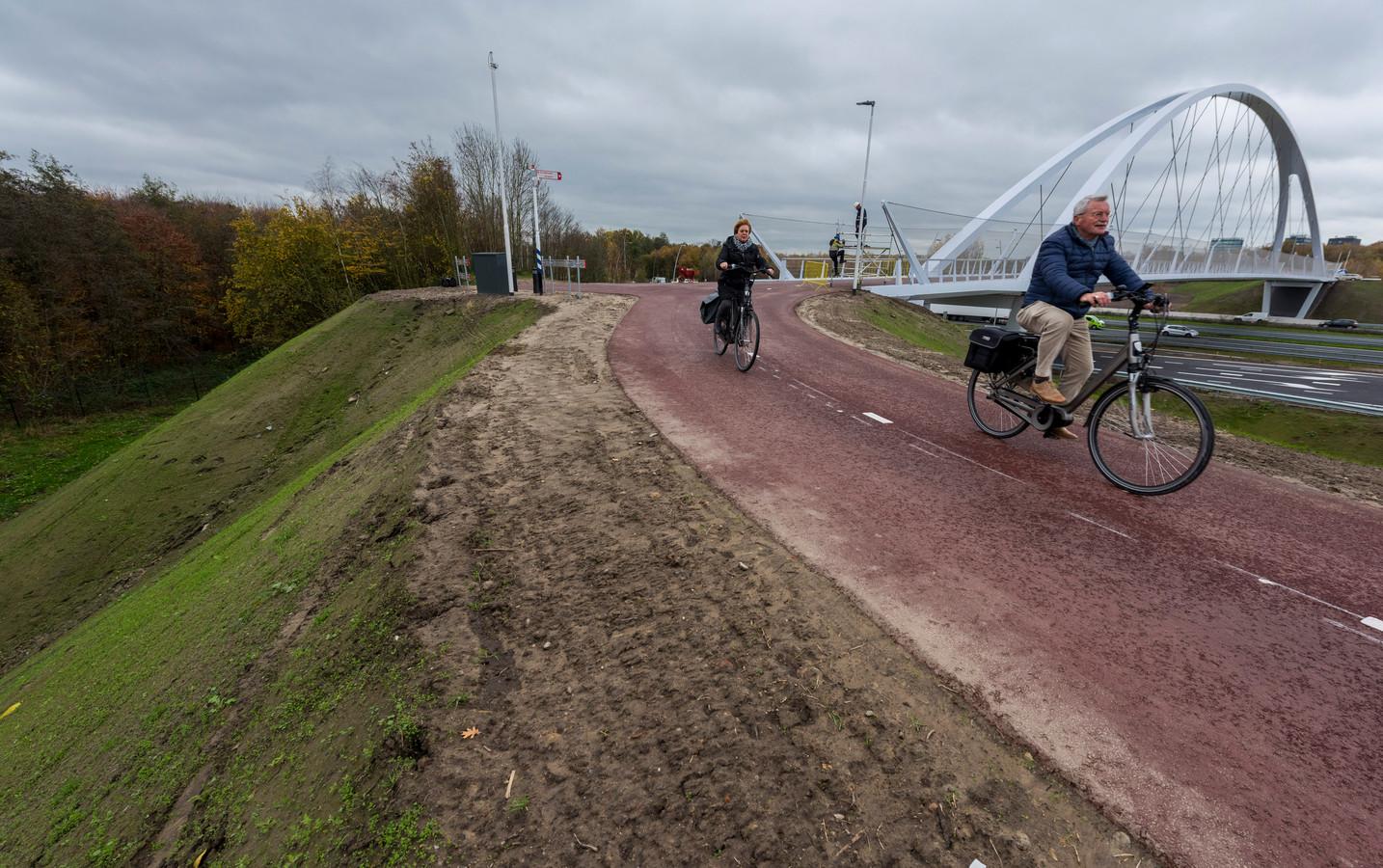 Fietsers die de fietsbrug over de A2 verlaten en de bocht maken. Langs het fietspad is het zeer steile en hoge talud zichtbaar.