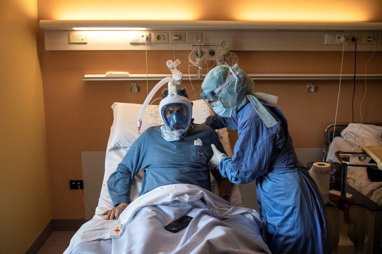 Medisch personeel helpt een patiënt die lijdt aan het coronavirus in het Maria Pia Ziekenhuis, Turijn. Beeld AFP