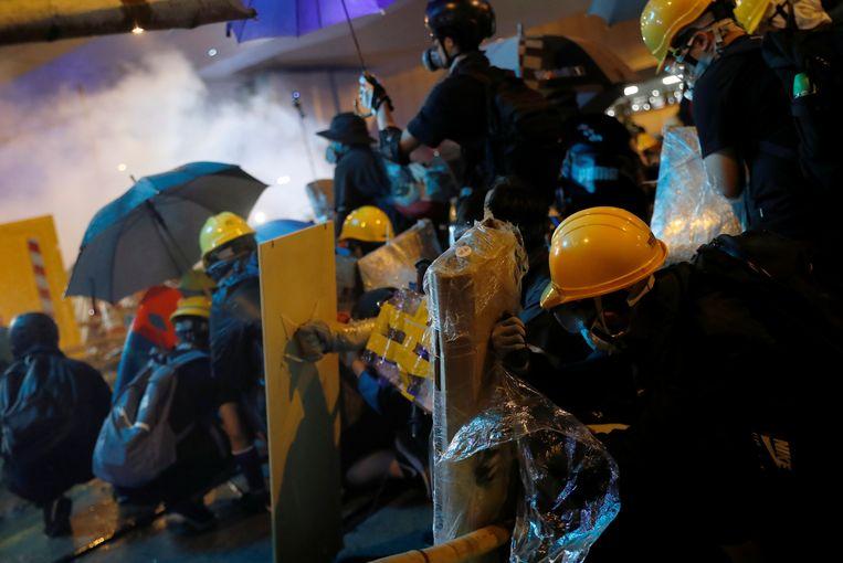 De demonstranten beschermen zich met paraplu's en mondmaskers tegen het traangas.