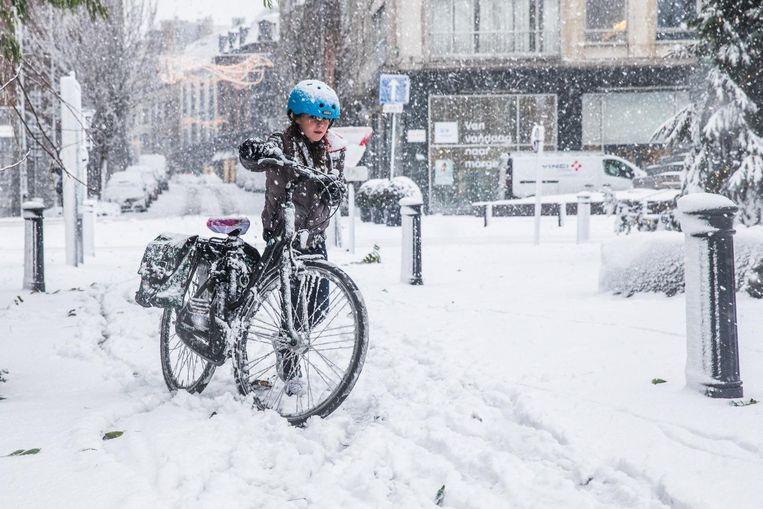 Met de fiets ploegen door de sneeuw aan het François Laurentplein in Gent.