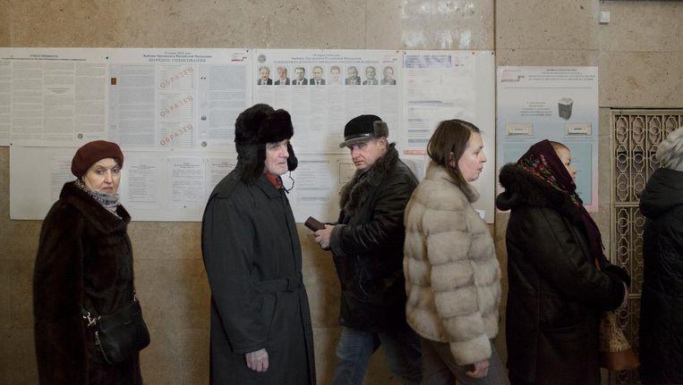 Russen staan in de rij om te stemmen in Moskou tijdens de presidentsverkiezingen. Beeld Emile Ducke