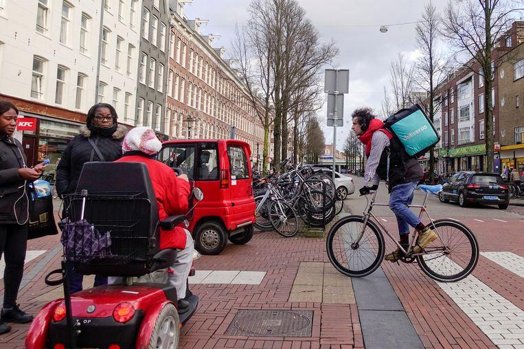 Nederland, Amsterdam, een deliveroobezorger op het voetpad met zijn fiets in Amsterdam 1 februari 2018, foto: Katrien Mulder Beeld Hollandse Hoogte / Katrien Mulder