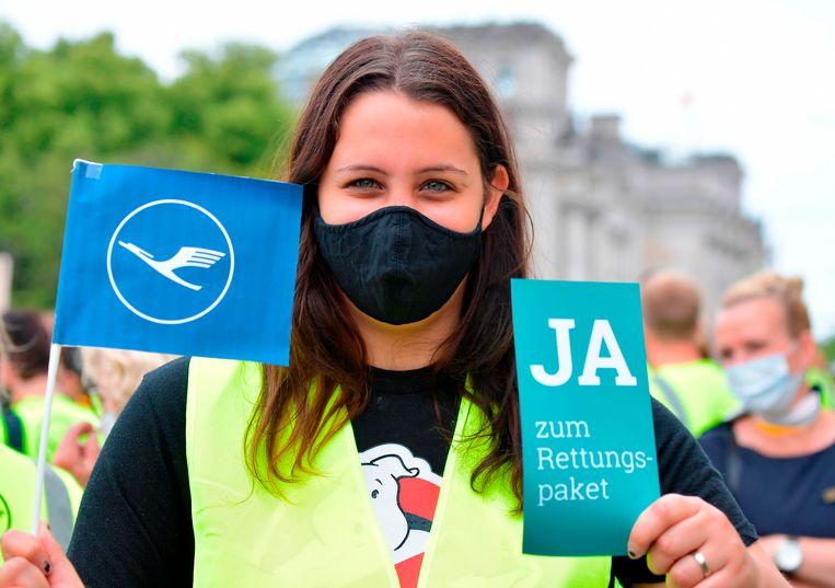 Een werknemer van Lufthansa demonstreert in Berlijn. 'Ja aan het reddingspakket' staat er op het bordje geschreven.