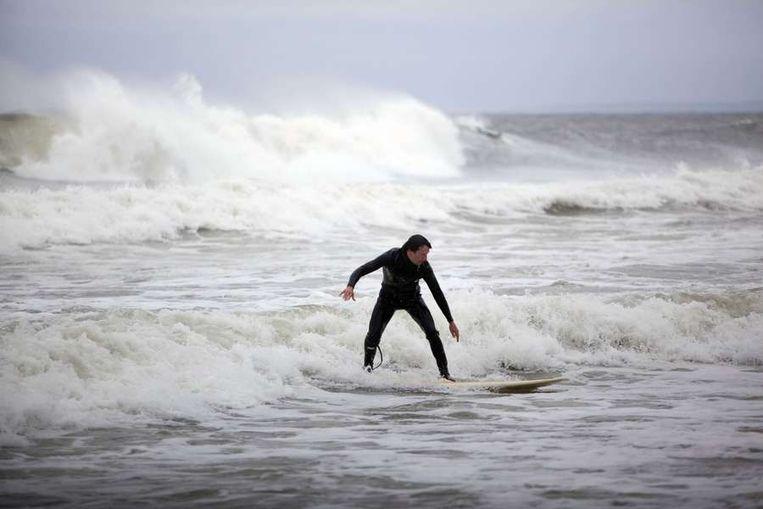 Een surfer profiteert van de hoge golven.