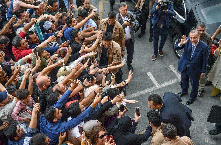 Aanhangers juichten de Turkse president Erdogan zondag toe, toen hij het stembureau verliet. Beeld AFP