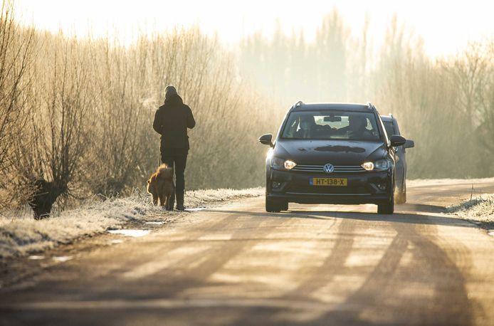 Automobilisten en een voetgang over een weg met ijzel. Door de strenge nachtvorst is er door het KNMI in grote delen van het land code oranje afgegeven voor gladheid op de wegen.