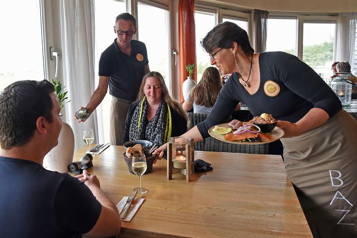 Gastheer Marco schenkt de wijn in en gastvrouw Ingrid dient de salade op.
