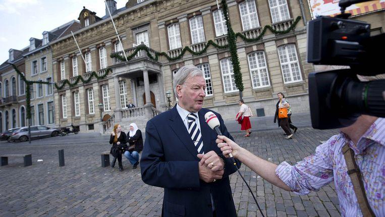 Burgemeester Henk van Beers van Roermond staat voor het stadhuis de pers te woord, vrijdag. Beeld ANP