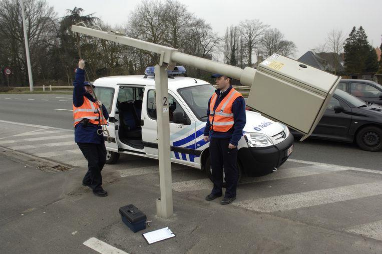 Christel en Henk, van de Gentse politie: 'Soms staan hier in het kantoor vrouwen die  de flitsfoto willen controleren, maar in feite willen ze vooral zien of hun man alléén in de wagen zat.' Beeld Stephan Peleman