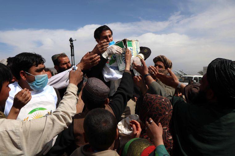 Een gezondheidsmedewerker deelt mondmaskers, handschoenen en desinfecteergel uit in Afghanistan.