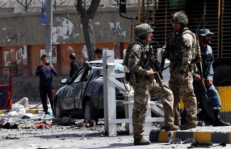 Troepen van de NAVO-Resolute Support Mission inspecteren de plaats waar de autobom donderdag ontplofte. Beeld EPA