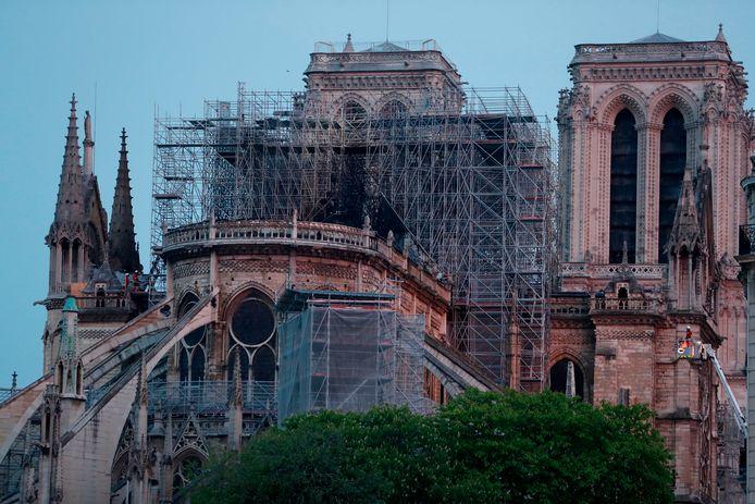 Uiterst rechts op de foto: brandweermensen gaan met een hoogwerker de Notre-Dame binnen.