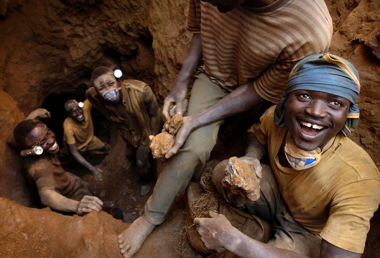 Jongemannen in een kopermijn in de omgeving van Lumbumbi in Congo. In dit land werken naar schatting 40.000 kinderen in de mijnindustrie. Beeld Hollandse Hoogte / Sven Torfinn