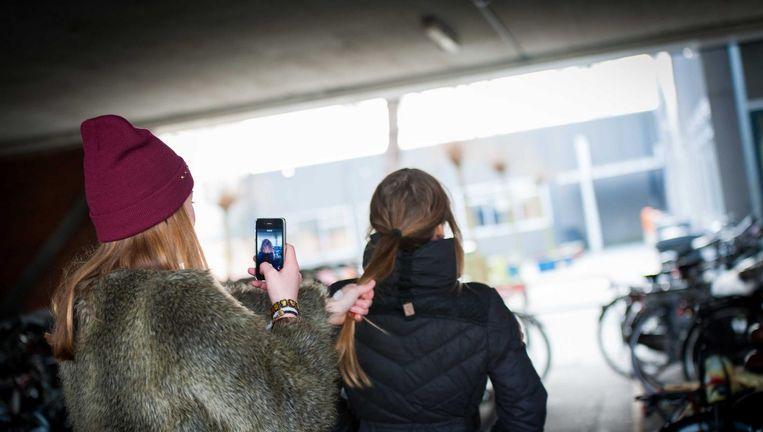 Een scholiere pest een schoolgenootje en filmt dit met een smartphone. Beeld null