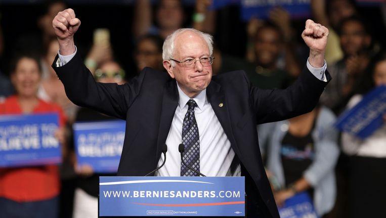 Bernie Sanders viert dinsdag zijn zege in Michigan. Beeld Alan Diaz / AP