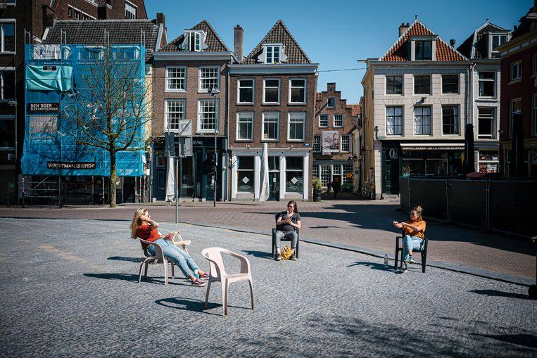Drie vrouwen zitten op gepaste afstand van elkaar in drie stoelen op het Neude in Utrecht. Beeld Hollandse Hoogte / Erik van 't Woud