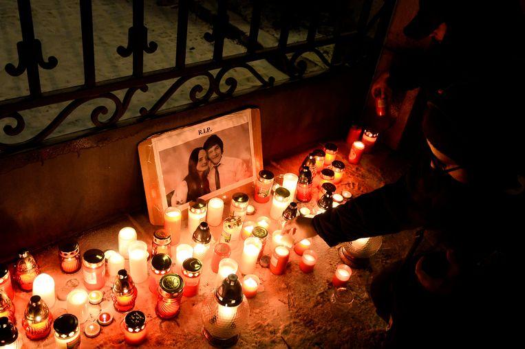 Mensen steken massaal kaarsjes aan bij de foto van Jan Kuciak en zijn vriendin aan het parlementsgebouw in Slovakije.