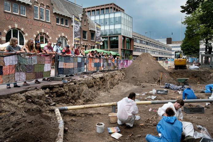 Kijkers naar graven op het kerkplein.