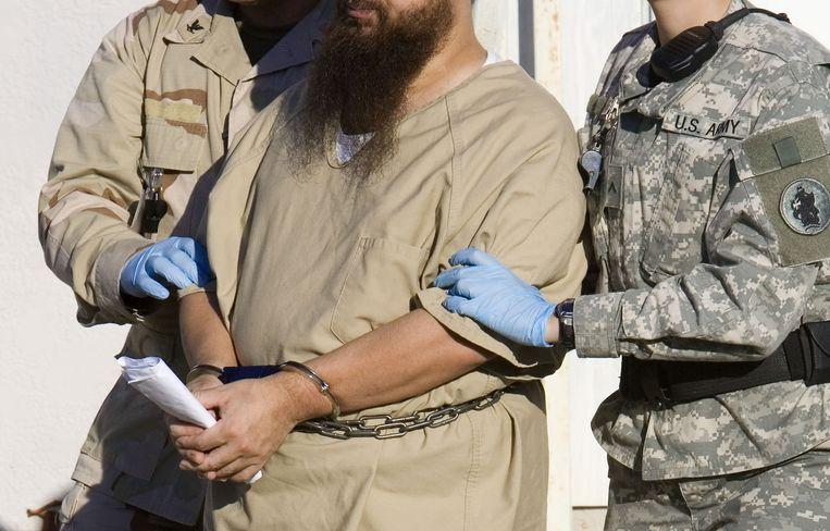Een gevangene op Guantánamo Bay wordt weggeleid. Beeld afp