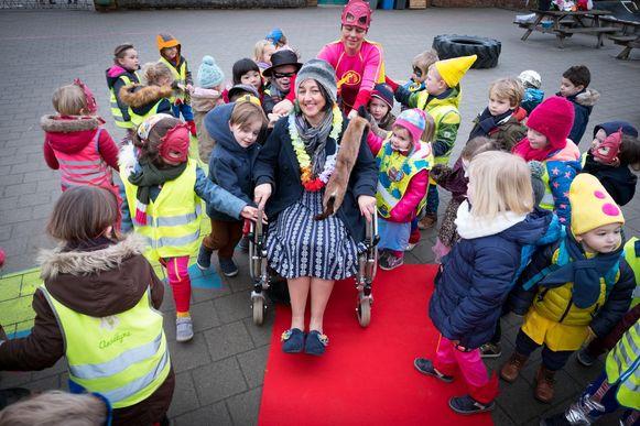 De jarige juf Martine (in oma-outfit) wandelde met een rollator naar school. Daar mocht de jonge vijftiger, tot groot jolijt van de kleuters, in een rolstoel plaatsnemen.