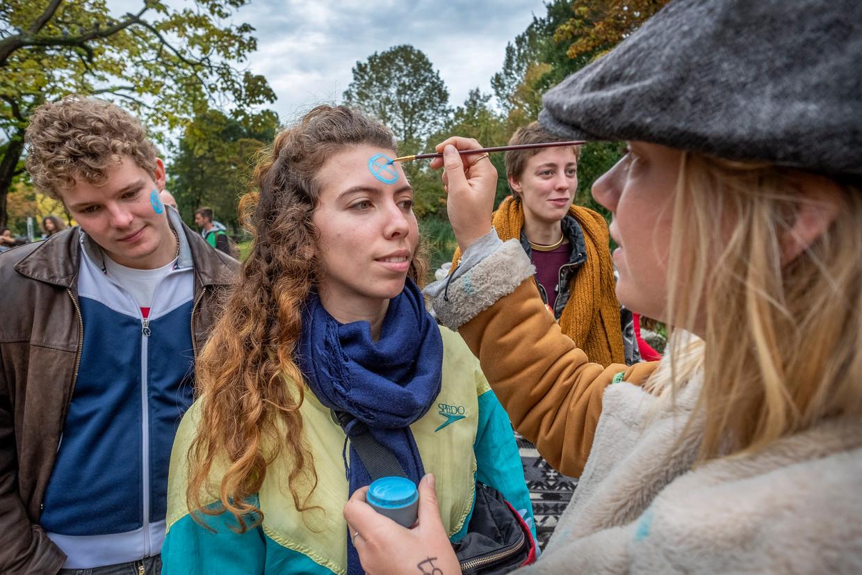 In het Vondelpark laten actievoerders het symbool van Extinction Rebellion, gebaseerd op een zandloper, op hun gezicht schilderen.