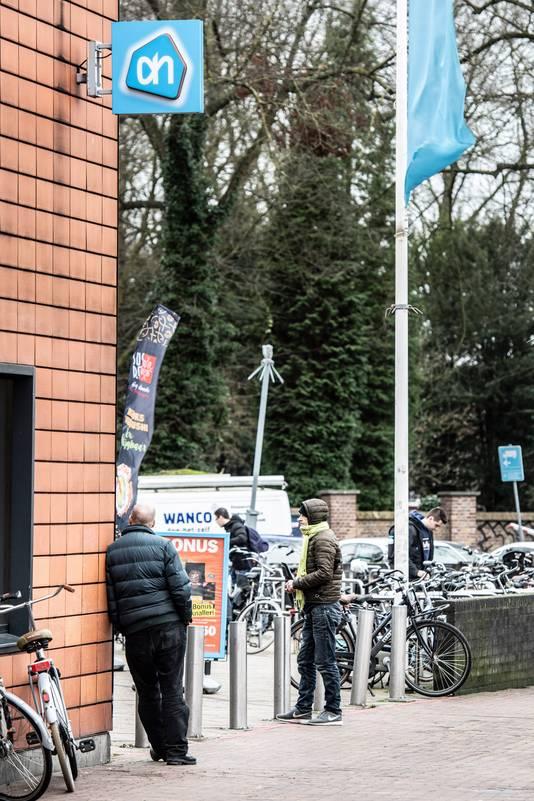 Een bedelaar wapent zich met muts en shawl tegen de elementen bij Albert Heijn aan de Daalseweg in Nijmegen.