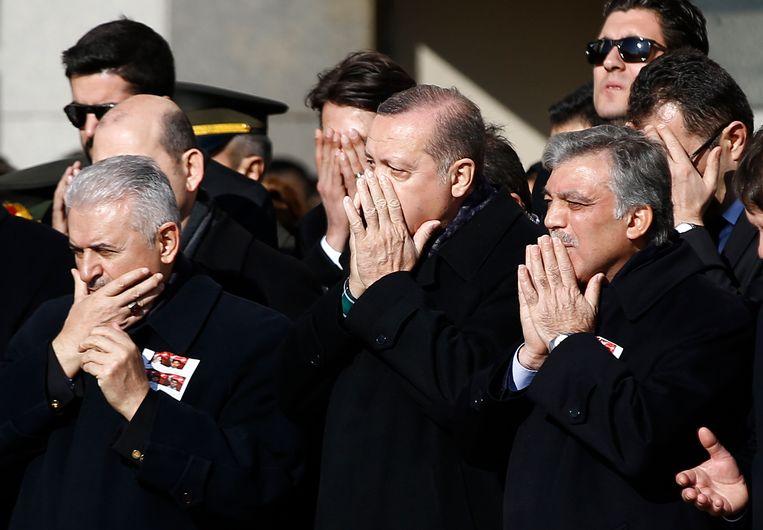 Erdogan (midden) tijdens een ceremonie voor de omgekomen politieagenten. Beeld AP
