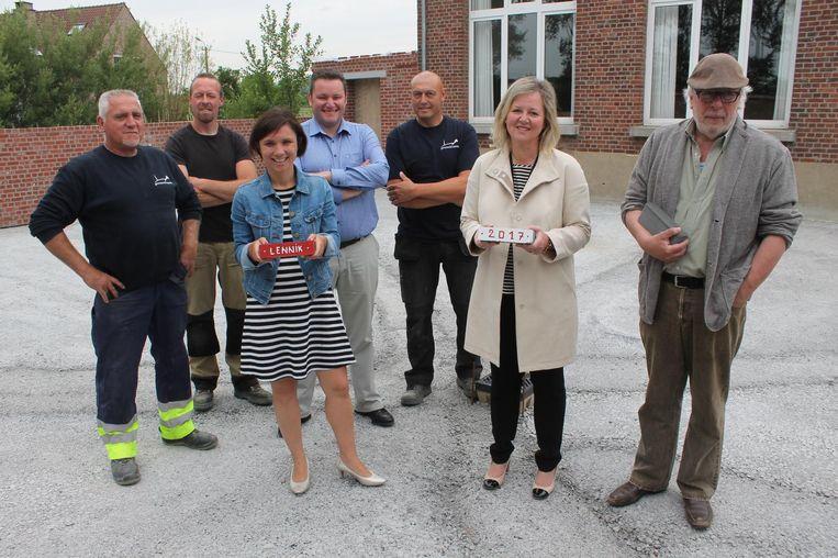 Burgemeester Irina De Knop, schepen Heidi Elpers en Hugo De Greef van de School van Gaasbeek staan klaar met de eerste stenen voor de heraanleg van de voormalige speelplaats.