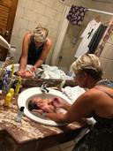 Baby Yassin wordt door oma Sylvia in bad gedaan.