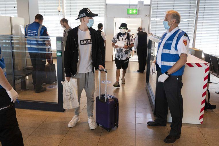 Medewerkers van de GGD ondervragen reizigers op Schiphol. Reizigers uit risicogebieden worden achter de douane gecontroleerd op coronaklachten. Beeld ANP