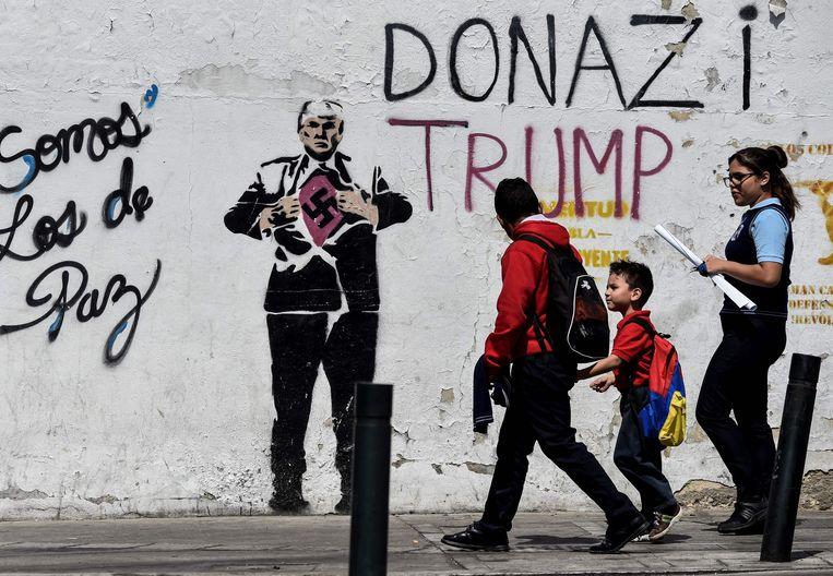 Een muurschildering in Caracas van de Amerikaanse president Trump die een t-shirt met een swastika - het symbool van nazi-Duitsland - onthult.