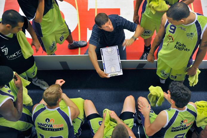 Michael Schuurs (met tactiekbord) instrueert zijn spelers bij Magixx.