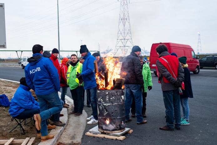 Arbeiders van chemiereus Bayer verwarmen zich aan een vuurtje.