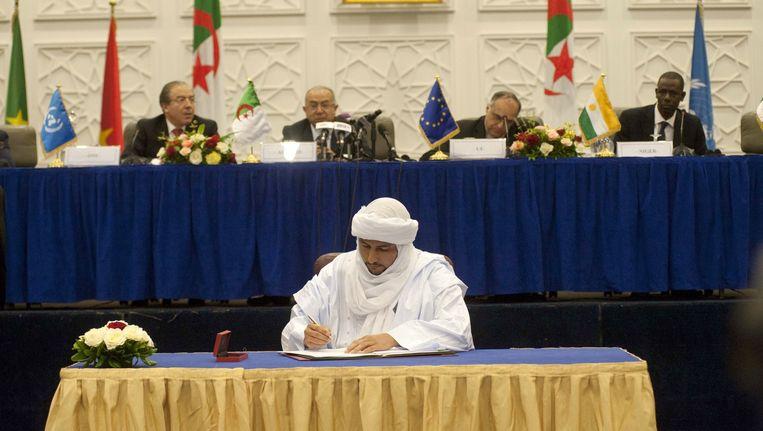 Bilal Ag Cherif tekent documenten tijdens de vredesakkoordceremonie in Mali. Beeld afp