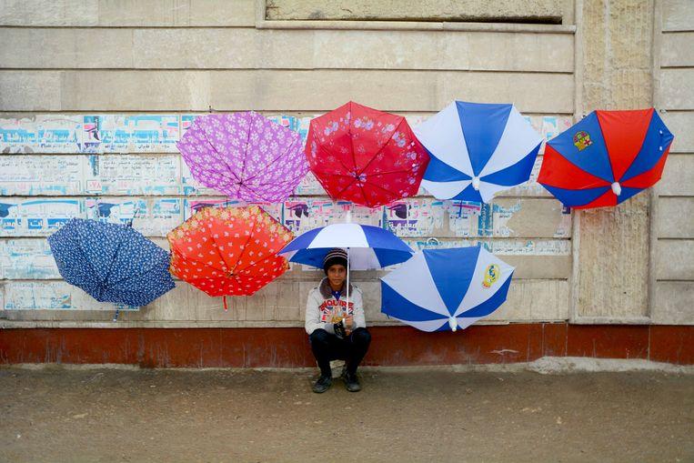 Regen is zeldzaam in mei, maar deze jonge verkoper in Bagdad grijpt zijn kans. Hij verkoopt paraplu's en blijft zo zelf ook droog. Beeld Munaf al-Saidy